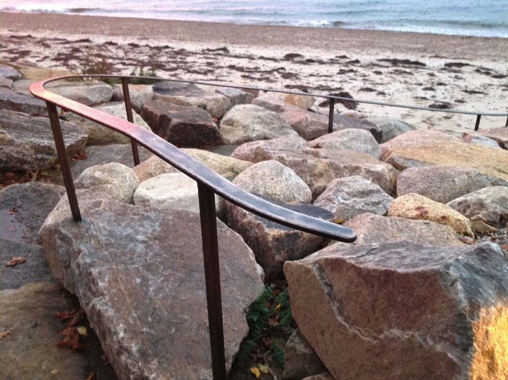 An ocean side handrail made from bronze to withstand the harsh salt environment.  Posts are set into large stones.